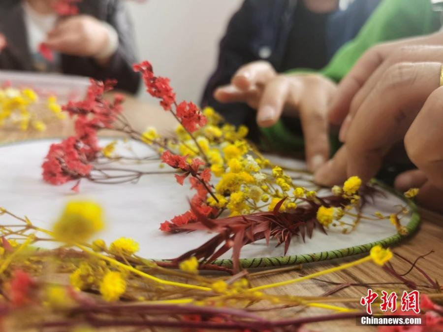 <p>People with disabilities and their families decorate the moon-shaped fan with dried flowers at a local community in Xining, northwest China's Qinghai Province, September 18, 2021. (Photo: China News Service/Zhang Tianfu)</p>