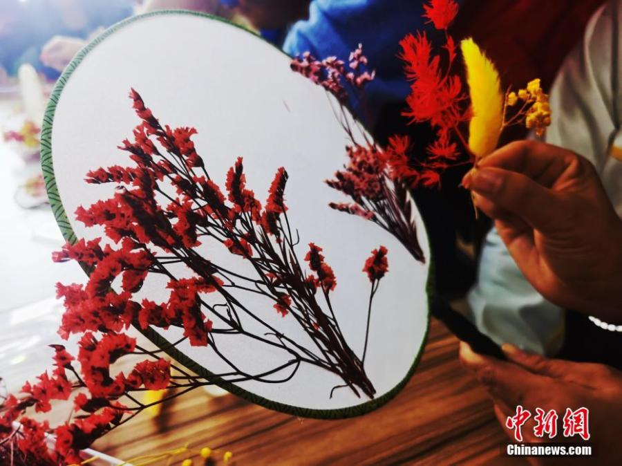 <p>A resident decorates the moon-shaped fan with dried flowers at a local community in Xining, northwest China's Qinghai Province, September 18, 2021. (Photo: China News Service/Zhang Tianfu)  </p>