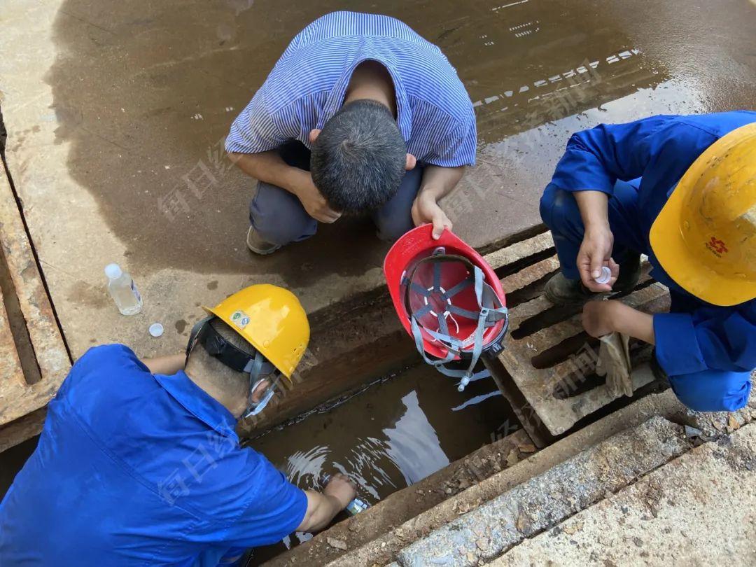 督察组工作人员在污酸处理车间雨水管道取样进行检测