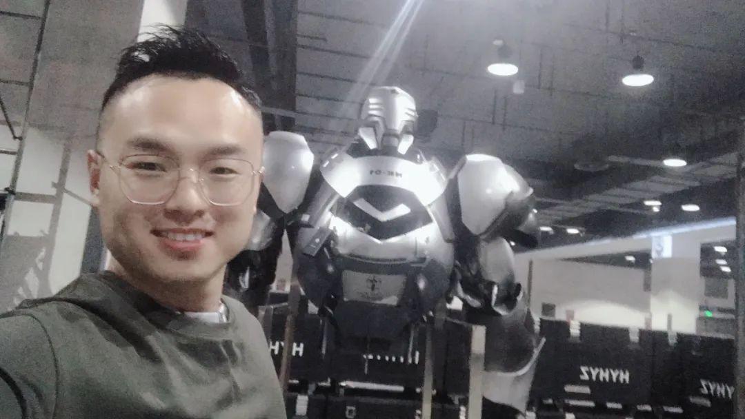 王铭在自己喜欢的机甲装备前合影。