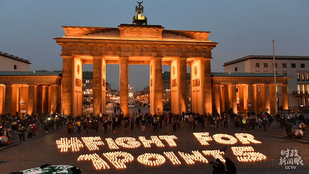 """△《巴黎协定》的设定目的之一是将环球升温幅度节制在1.5摄氏度以内。这是2020年12月11日,在德国柏林举办的怀念《巴黎协定》签订五周年运动,现场用蜡烛拼出""""为1.5摄氏度而战""""的标语。(图/视觉中国)"""
