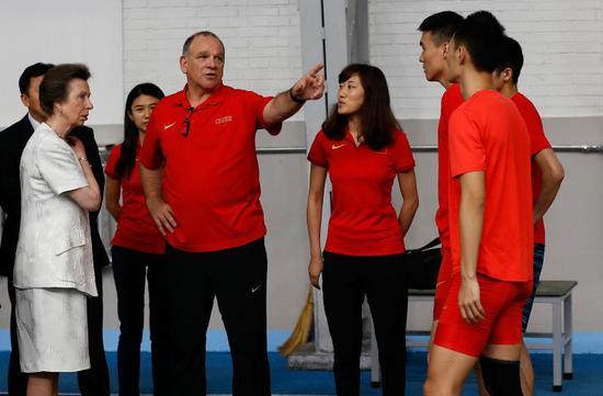 英国安妮公主(前左一)与中国田径队跳远外教兰道尔·亨廷顿(前左二)、运动员李金哲(右三)等交流。