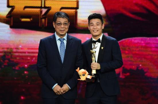 2018年11月21日,获得最佳射手奖的上海上港队球员武磊(右)在颁奖仪式上与足球名宿、颁奖嘉宾徐根宝合影。新华社记者杨冠宇摄