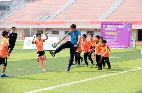 李金羽和孩子們在足球公益趣味賽中PK球技