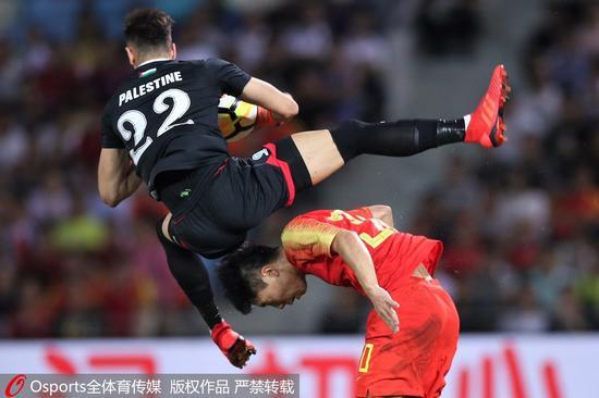 国足球员在场上拼抢。