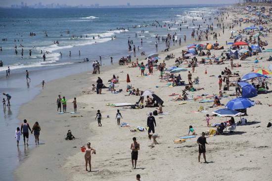 6月27日,人们在美国加利福尼亚州亨廷顿海滩游玩。