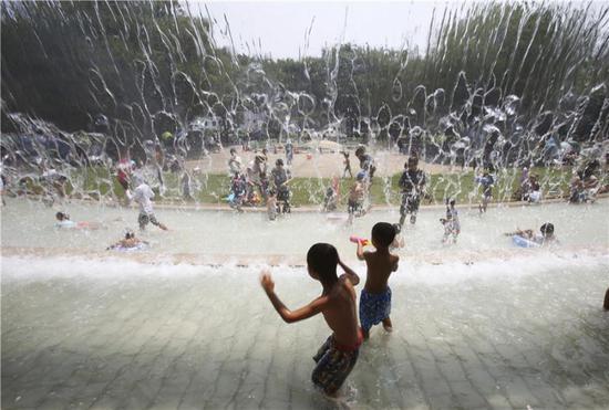 7月16日,在日本东京,孩子们在公园里的一处喷泉下玩耍。
