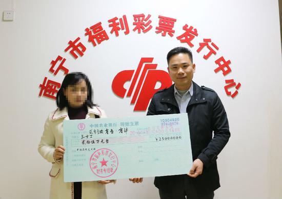 图为:南宁市福彩中心工作人员为王女士颁奖