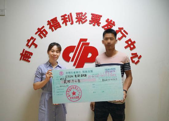 图为:南宁市福彩中心工作人员为刘先生颁奖