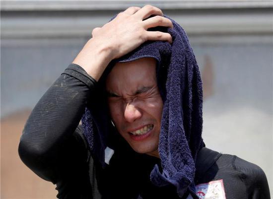 7月14日,在日本冈山县仓敷市,一名男子用毛巾擦汗。