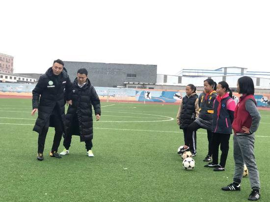 理事长刘成和理事樊海东为强蛟镇中心幼学的女足队员上足球公好课