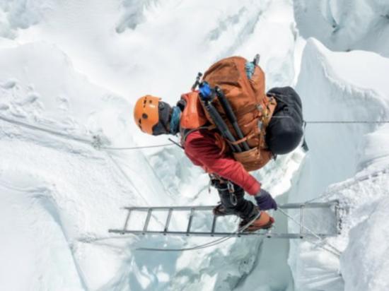 在尼泊尔的珠峰国家公园(Sagamartha),登山家越过冰川间的悬崖。