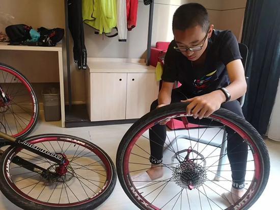 图为周子傲在自力维修自走车轮胎。周威供图