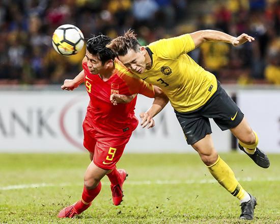 张玉宁(左)与马来西亚队球员拼抢.本文图片均来自新华社