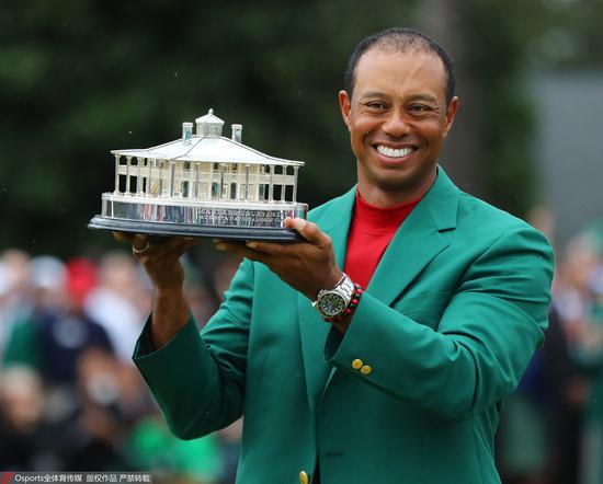 穿着绿夹克的伍兹手捧冠军奖杯。图/Osports