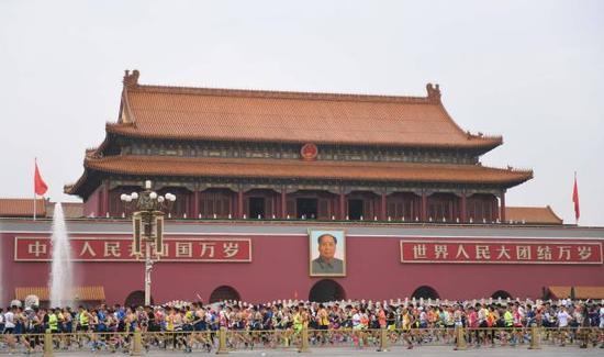 参赛选手在2016北京马拉松赛中经过天安门广场↑新华社记者孔卉摄