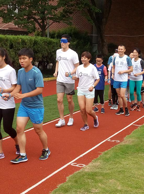 刘翔体验视障跑者的感受。实习生 王蕴玮 图