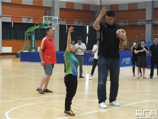 邓亚萍向姚明请教打篮球。(央广网记者 吴凯 摄)