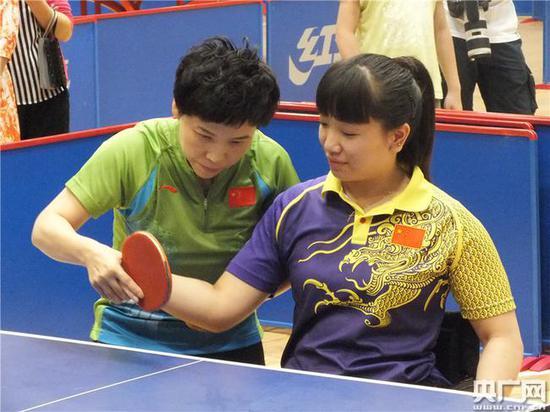 邓亚萍在悉心指导技术动作。(央广网记者 吴凯 摄)