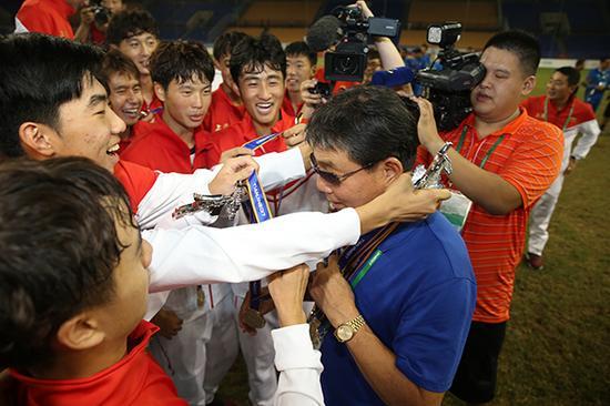 2017全运会U18男足上海 队夺冠后,队员把金牌挂在老帅徐根宝的脖子上。