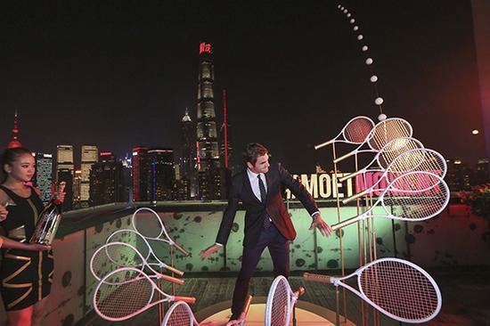"""2017年10月7日,2017上海大师赛,费德勒出席活动。费德勒握着球拍向着浦江对岸的上海中心""""击出""""一球。"""