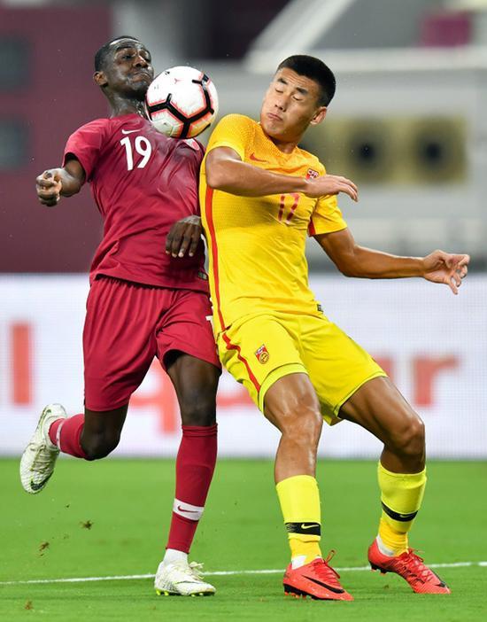 卡塔尔队球员阿尔莫兹·阿里(左)与中国队球员张呈栋在比赛中争抢。