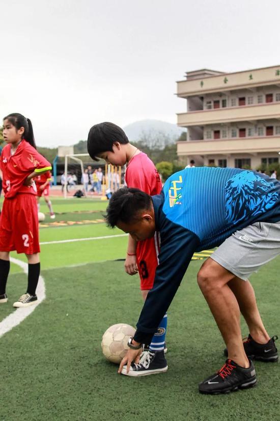 陈志钊、黄政宇对小球员进行指导。