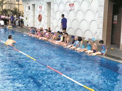 游泳館裏參加培訓的小朋友準備上課。