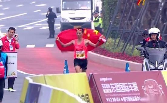 南宁马拉松选手举国旗冲线。