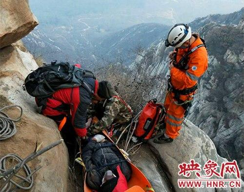 救援人员依靠岩壁上的岩缝一点一点向山顶移动