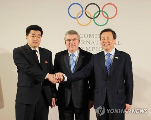 当地时间1月20日,在瑞士洛桑,朝鲜体育相金一国(左起)、国际奥委会主席巴赫、韩国文化体育观光部长官都钟焕合影。(韩联社)