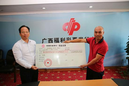 2017年,广西福彩中出大量大奖,广西福利彩票发行中心副主任梁卫(左)为中奖者颁发支票