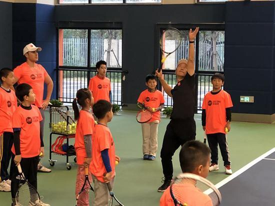 张德培指导小朋友打球。