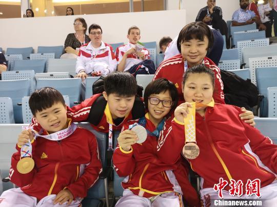 李小奇(左)与游泳队的小伙伴们分享快乐。卞颖提供