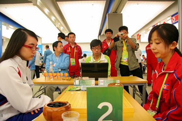 ▲ 2010年亚运会,中国台湾棋手黑嘉嘉与朝鲜棋手赵新星在对局。当时,朝鲜队的教练是李凤日。