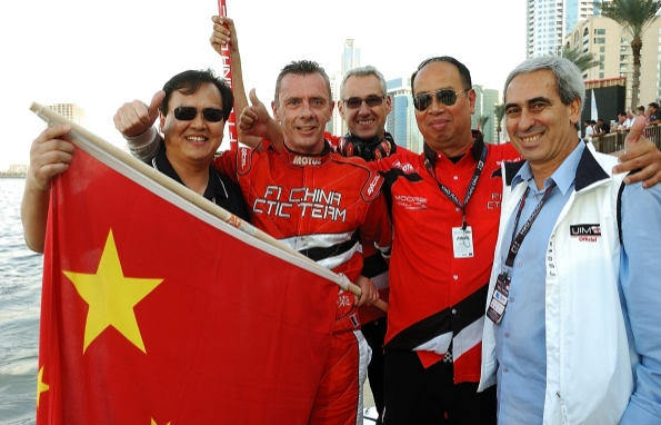 2014赛季,国际摩联F1委员会委员李浩杰(左一)手持国旗,祝贺中国天荣队荣膺年度总冠军