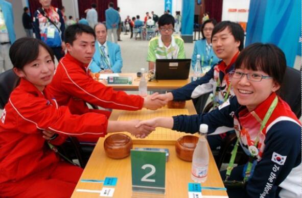 2010年广州亚运会,在围棋混双项目比赛前,朝鲜的朴虎吉、赵新星组合与韩国崔哲瀚、金仑映组在握手。