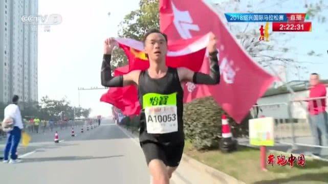 """志愿者在百米冲刺时给力争冠军的中国选手递送国旗是""""奔跑中国""""马拉松图片"""