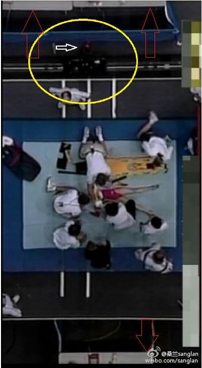 (上图:我受伤后,前来救援和急救的场景。而罗马尼亚教练仍然停留在右下方。 红色箭头的部分指的是桌子,这个从第一张图中就可以看出桌子的高度和形状。上一张图中的卷曲直立的物体与垫子颜色接近,符合我在第一跳时候对于那块垫子的记忆。而这张俯视图中这个物体显然没有了,否则一定是可以拍到的。我猜测:是那块物体遮挡了通道,因此被挪移开了)