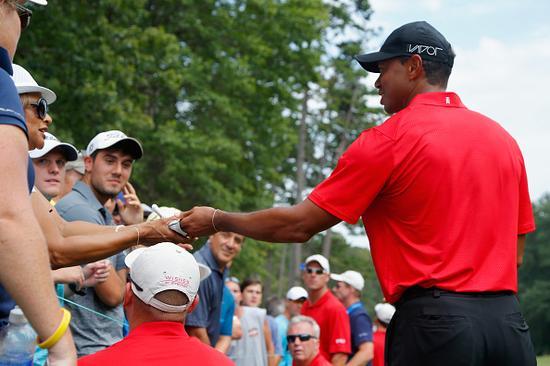 伍兹在球迷的高尔夫球上签名
