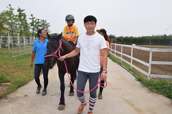 塔林呼(白色T恤)为视障儿童牵马