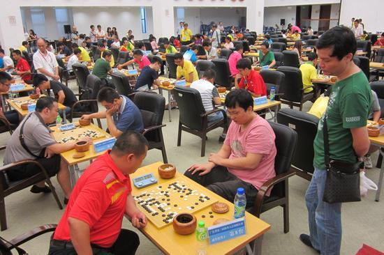 2013年林斯达(右二)代表汕头参加广东省第三届体育大会围棋赛,教练蔡建鹏旁观