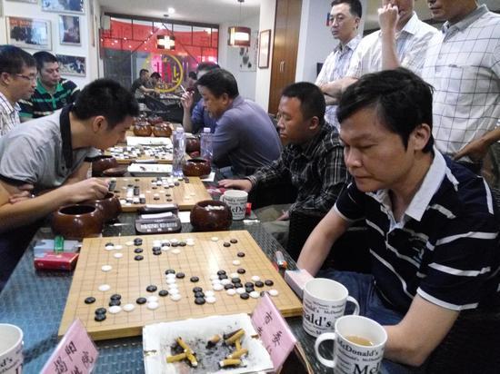 2015年汕头围甲联赛,蔡建鹏(右一)与弟子李聪(右二)、陈景聪(左一)同场竞技