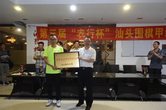 方扬(左)向冠名支持赛事的农业银行代表陈云颖赠送牌匾