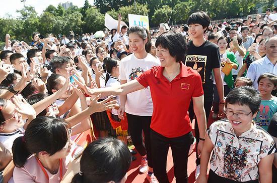 9月17日,中国女排主教练郎平与学生互动。新华社 图