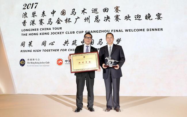 香港赛马会市场及客户事务执行总监张之杰(左)与广东省体育局副局长许建平(右)在欢迎晚宴上交换纪念品