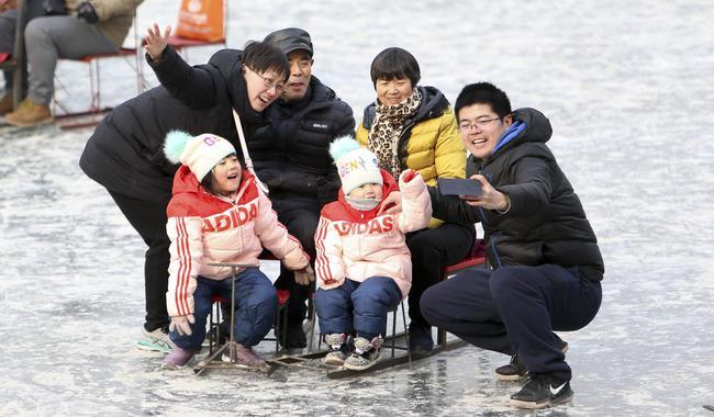 12月31日,游客在北海公园冰场自拍留念。
