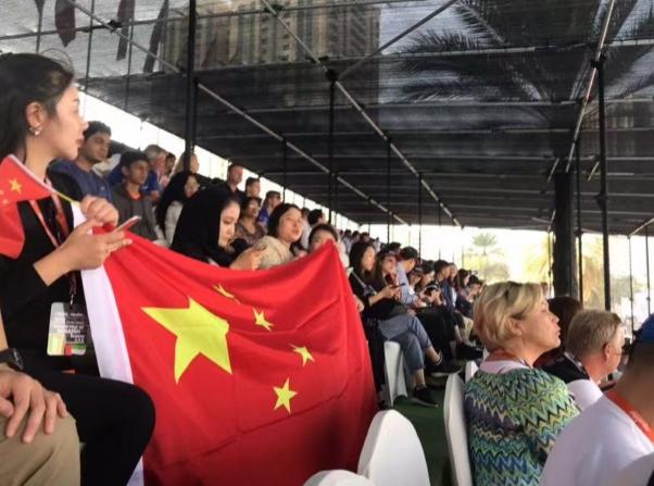 海外华人华侨恭维团在望台上拉首国旗为中国天荣队添油恭维