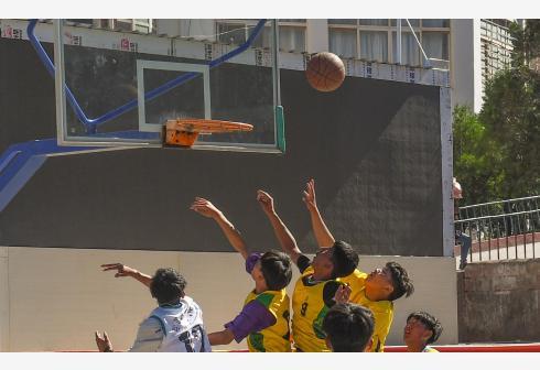 盐井中学的学生们在体育课上打篮球