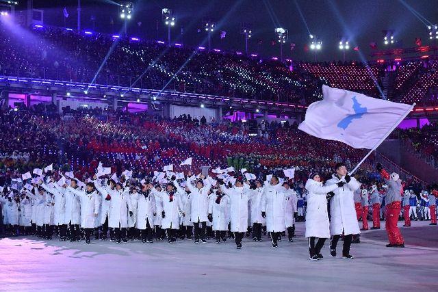 """朝韩两国代表团在平昌冬奥会开幕式上举""""朝鲜半岛旗""""共同入场。 新华社记者吕小炜摄"""